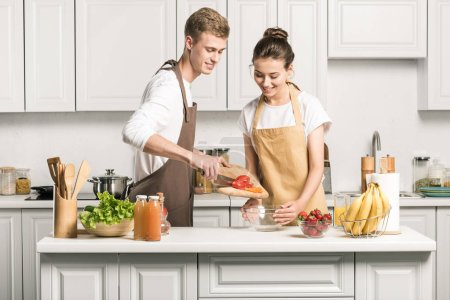 young couple cooking salad and putting healthy vegetables in bowl in kitchen