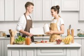 """Постер, картина, фотообои """"Молодая пара приготовления салата и проведение бумажное полотенце в кухне"""""""