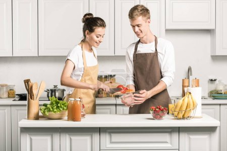Photo for Young couple cooking salad and putting vegetables in bowl in kitchen - Royalty Free Image
