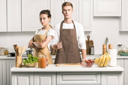 Photo for Serious young couple looking at camera in kitchen - Royalty Free Image
