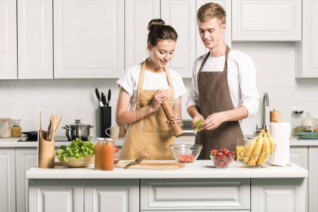 young couple cooking salad and adding spices in kitchen