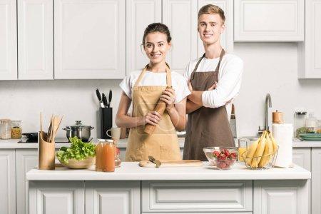 Photo pour Jeune couple en tabliers en regardant la caméra dans la cuisine - image libre de droit