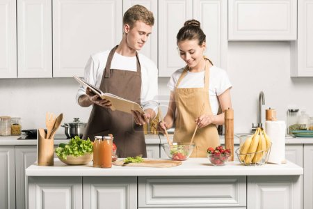 young couple cooking salad with recipe book in kitchen