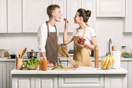 Photo pour Petite amie alimentation copain avec fraise dans la cuisine - image libre de droit