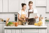 young couple cooking pasta and using laptop in kitchen