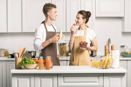 Photo for Young couple eating healthy fruits and looking at each other in kitchen - Royalty Free Image