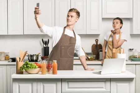 Photo for Boyfriend taking selfie with smartphone in kitchen - Royalty Free Image