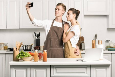 Photo for Young couple taking selfie with smartphone in kitchen - Royalty Free Image