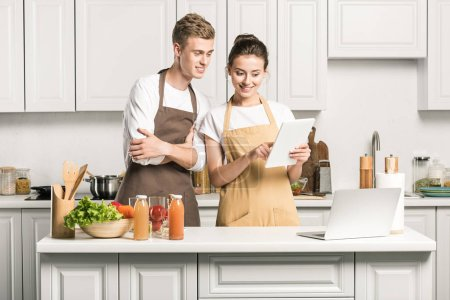 young couple looking at tablet in kitchen