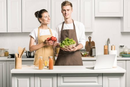 young couple cooking salad and standing with vegetables in kitchen