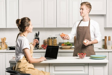 Photo for Girlfriend using laptop, boyfriend holding bottles of juice in kitchen - Royalty Free Image
