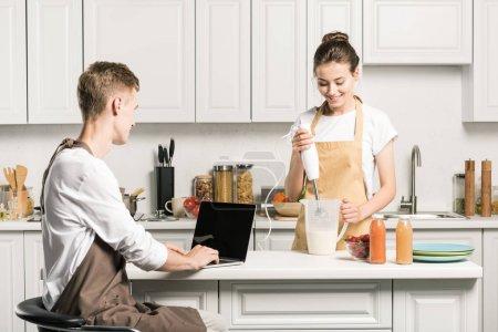 Photo pour Petit ami utilisant un ordinateur portable, petite amie préparant milkshake dans la cuisine - image libre de droit