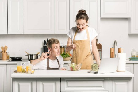 Photo for Young couple adding seeds to salad in kitchen - Royalty Free Image