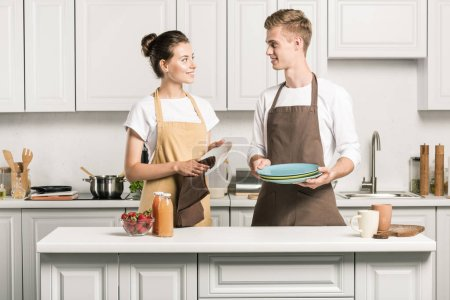 young couple drying dishes in kitchen