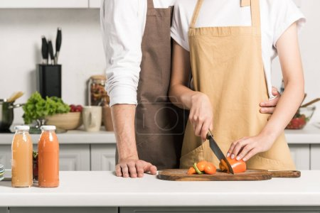 Photo for Cropped image of couple cooking salad and cutting tomatoes in kitchen - Royalty Free Image