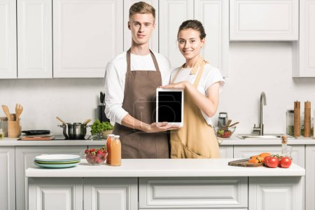 young couple holding tablet with blank screen in kitchen