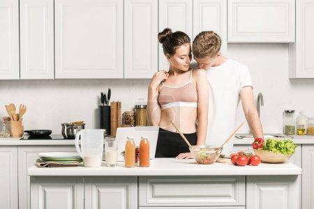 boyfriend kissing girlfriends shoulder in kitchen
