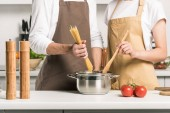 cropped image of young couple cooking pasta in kitchen
