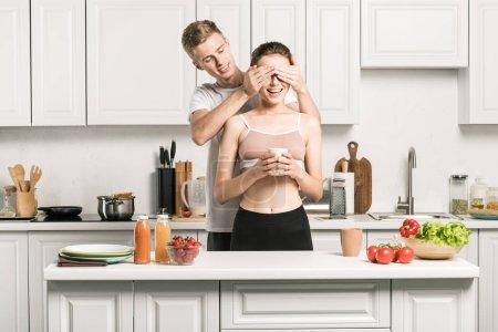 Photo pour Petit ami en fermant les yeux à la copine dans la cuisine - image libre de droit