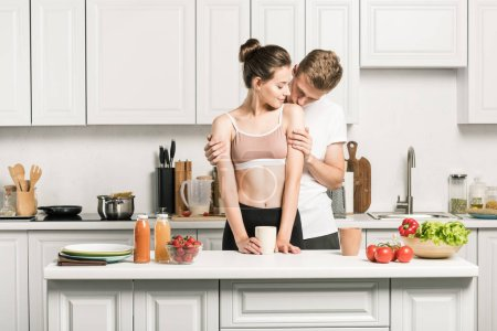 boyfriend kissing girlfriends shoulder in kitchen
