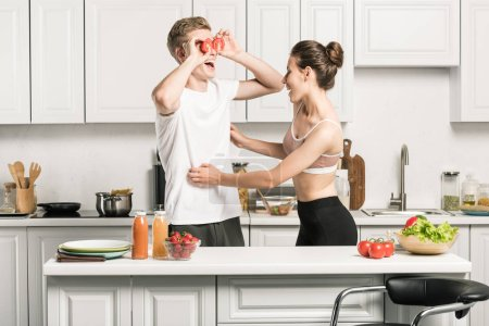 Photo for Young couple having fun while cooking pasta in kitchen - Royalty Free Image