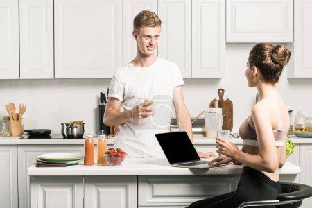 boyfriend holding glass of milk and girlfriend using laptop in kitchen