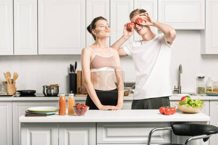 young couple having fun while cooking pasta in kitchen