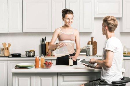 Photo pour Lait verser de petite amie et son copain à l'aide de tablette dans la cuisine - image libre de droit