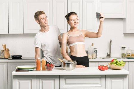 Photo pour Petite amie dans le soutien-gorge de sport prenant selfie smartphone dans cuisine - image libre de droit