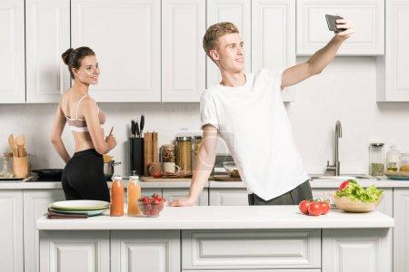 Photo pour Petit ami prenant selfie smartphone dans cuisine - image libre de droit