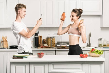 boyfriend taking photo of girlfriend with bottles of healthy juice in kitchen