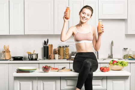 happy attractive girl sitting on kitchen counter and showing healthy juice in bottles
