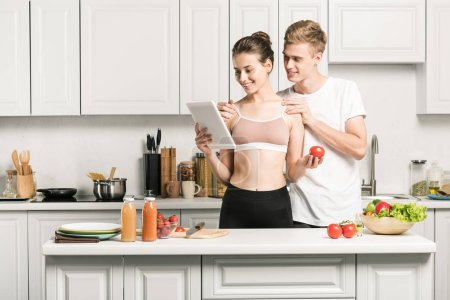 young couple reading recipe for healthy food on tablet in kitchen