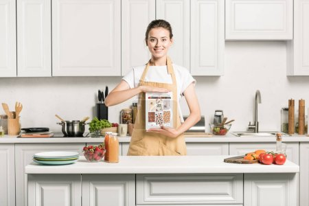 attractive girl holding tablet with loaded pinterest page in kitchen