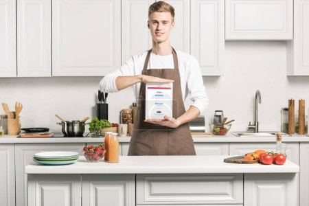 handsome man in apron showing tablet with loaded instagram page in kitchen