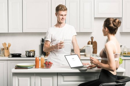 girlfriend using laptop with loaded google page and looking at boyfriend in kitchen