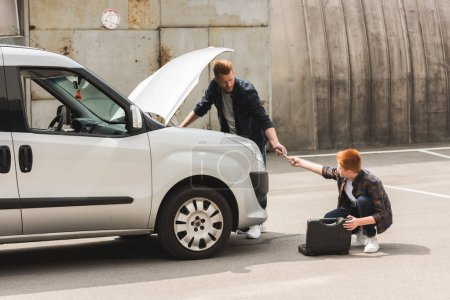 Photo for Side view of ginger hair son giving tool for repairing car to father - Royalty Free Image