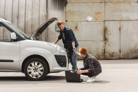 side view of son giving tool for repairing car to father