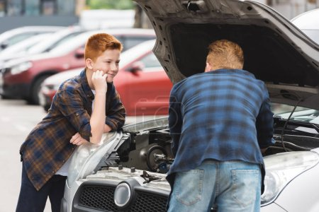 Photo for Son looking how father repairing car with open hood - Royalty Free Image