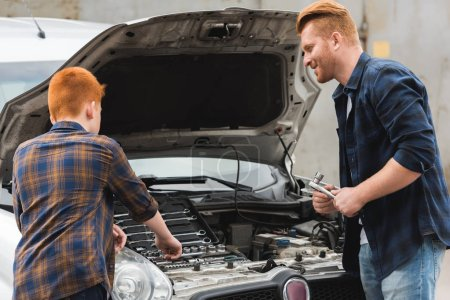 Photo pour Cheveux roux père et fils, réparation de voiture avec le capot ouvert - image libre de droit