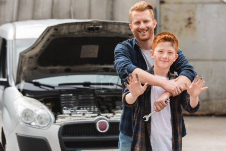 father hugging son after repairing car and he waving hand