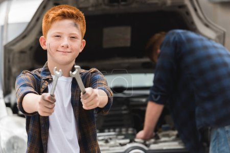 father repairing car with open hood, son showing tools