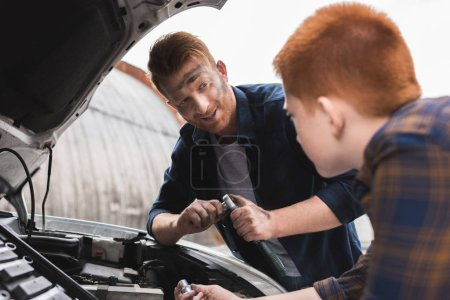 father and son repairing car with open hood and looking at each other