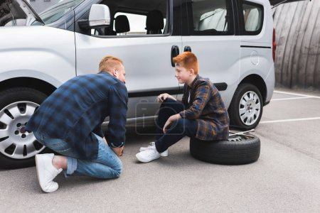 father lifting car with floor jack for changing tire and looking at son
