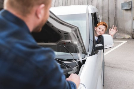 father repairing car with open hood, son waving hand