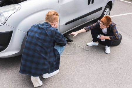 father lifting car with floor jack for changing tire, son pointing on something