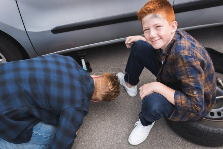 father lifting car with floor jack for changing tire, happy son looking at camera