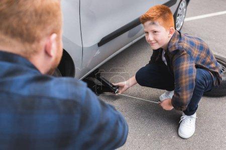 Photo pour Fils avec cric de levage voiture pour changer de pneus et regardant père - image libre de droit