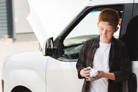 Photo for Red hair preteen boy repairing car and holding napkin - Royalty Free Image