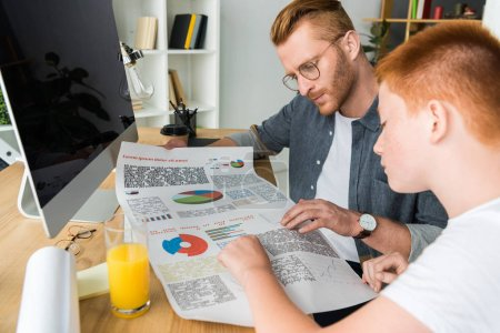 father and son looking at diagram at table at home